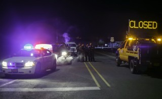 Law enforcement personnel monitor an intersection of closed Highway 395 in Burns, Oregon on January 26, 2016, during a standoff pitting an anti-government militia against the US authorities. One person died in an armed clash with police as they arrested the leaders of a group laying siege to an American wildlife refuge, the FBI said January 26. AFP PHOTO / ROB KERR / AFP / ROB KERR        (Photo credit should read ROB KERR/AFP/Getty Images)