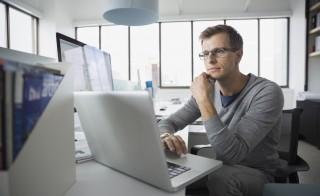 Focused worker writing at laptop computer in office