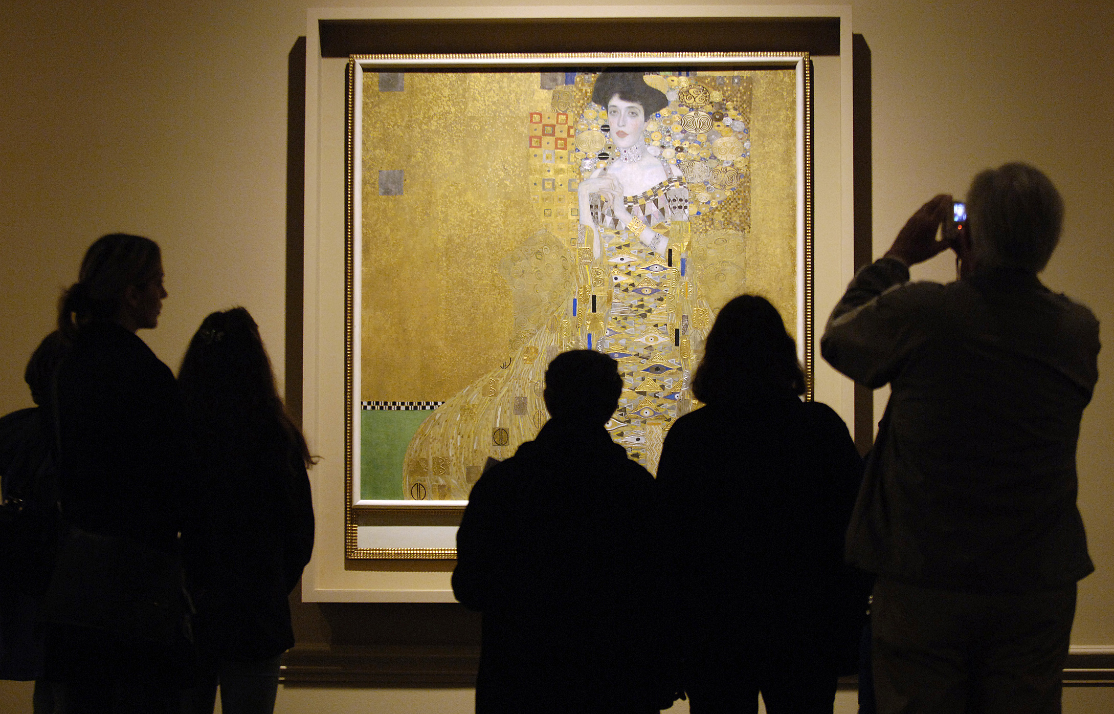 "Museum visitors study ""Adele Bloch-Bauer I,"" a 1907 painting by Austrian artist Gustav Klimt at a special exhibition of Klimt paintings looted by the Nazis during World War II, at the Los Angeles County Museum of Art in Los Angeles, April 4, 2006. Los Angeles resident Maria Altmann won the return of the paintings from the Austrian government following a lengthy legal dispute over the rightful ownership of the paintings.  REUTERS/Chris Pizzello - RTR1C6Z2"