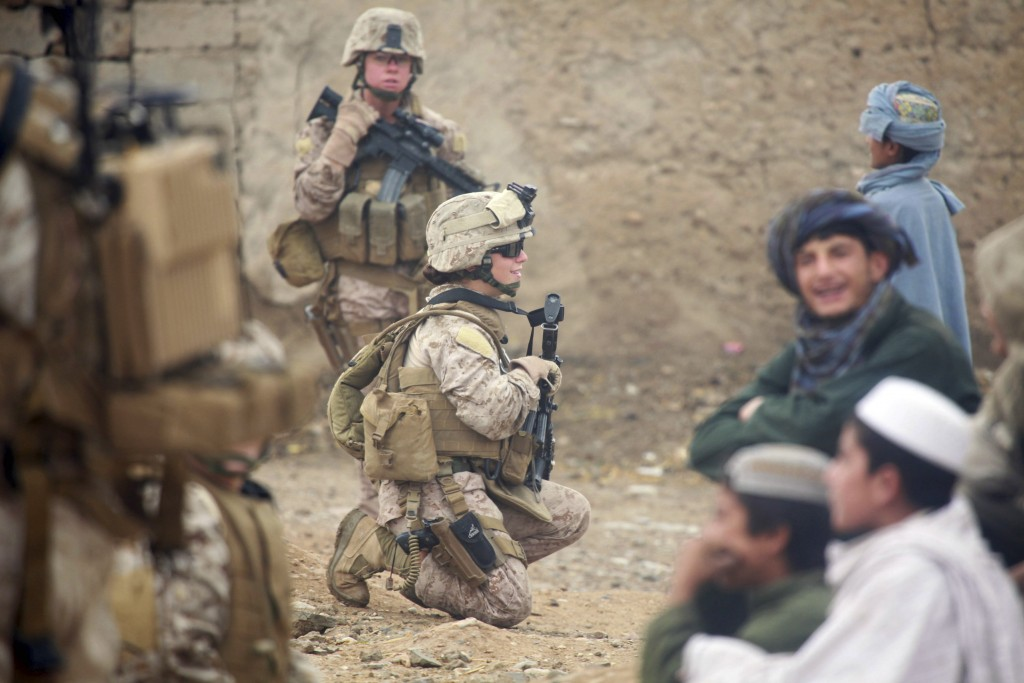 U.S. Marine Corps Lance Cpl. Sienna De Santis and U.S. Navy Petty Officer Heidi Dean, both with Female Engagement Team, greet children during a patrol in Sangin Valley, Afghanistan in Oct. 29, 2010. Photo By David Hernandez/Reuters