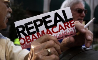 "A small group of demonstrators stand outside of a HIlton Hotel prior to a ""Defund Obamacare Tour"" rally in Indianapolis, on Aug. 26, 2013. President Barack Obama on Friday vetoed legislation to repeal his health care law, the first time such a bill made it all the way to the White House. Photo by Nate Chute/Reuters"