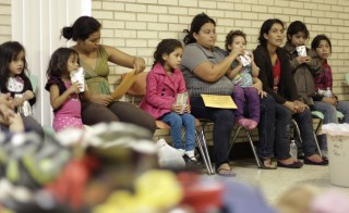Migrants sit at the Sacred Heart Catholic Church temporary migrant shelter in McAllen, Texas on June 27, 2014. The Sacred Heart Catholic Church has a temporary shelter where detained immigrants, most of them fleeing violence from their Central American countries, have been taken for temporary food and shelter after being ordered to appear in immigration court, local media reported. Photo by Stringer/Reuters