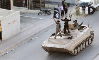 Militant Islamist fighters take part in a military parade along the streets of northern Raqqa province on June 30, 2014. Photo by Stringer/Reuters