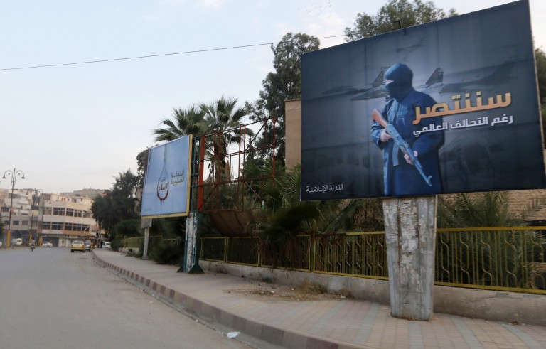 "Islamic State billboards are seen along a street in Raqqa, eastern Syria, which is controlled by the Islamic State, Oct. 29, 2014. The billboard (R) reads:  ""We will win despite the global coalition."" Photo by Nour Fourat/Reuters"