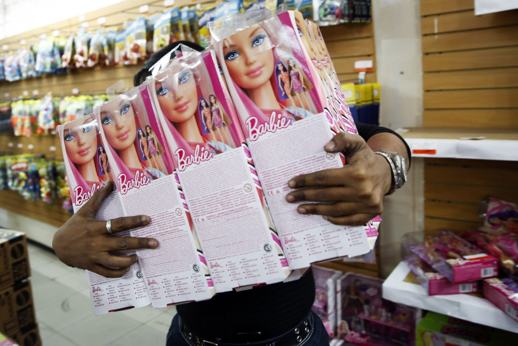 File photo of worker stocking shelves with Barbie dolls by Carlos Garcia Rawlins/Reuters