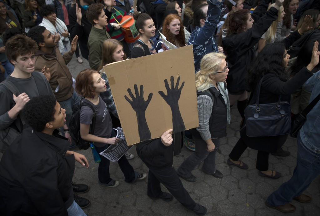 "A man marches with a sign depicting raised hands as students and activists hold a protest march through Manhattan, New York, against the verdict announced in the fatal shooting death of Michael Brown. Since President Barack Obama's election in 2008, polls have shown an overall decrease in the number of people who believe race relations are ""very or fairly good.""Photo by Mike Segar/Reuters"