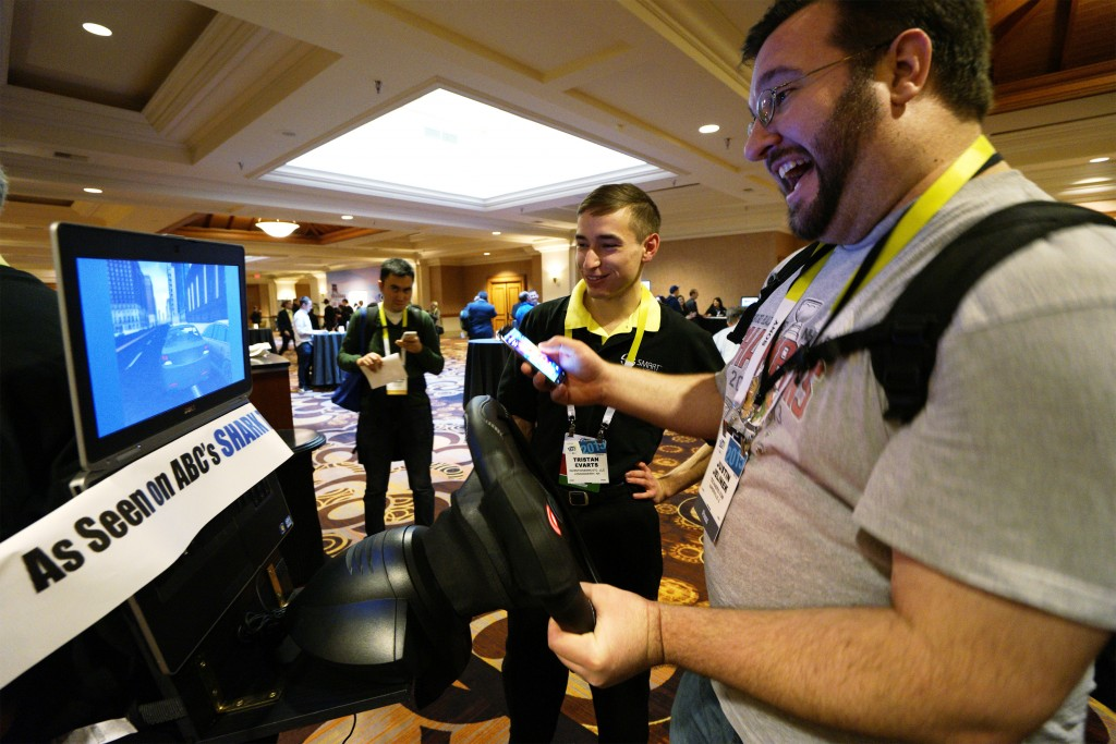Tristan Evarts (L), inventor of the SMARTwheel, demonstrates his product to Justin Jelinek at the International Consumer Electronics show (CES) in Las Vegas, Nevada January 4, 2015. The SMARTwheel is a steering wheel cover with sensors to prevent distracted driving.   REUTERS/Rick Wilking (UNITED STATES - Tags: BUSINESS SCIENCE TECHNOLOGY) - RTR4K1TK