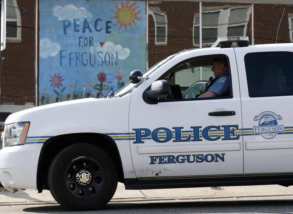 A Ferguson Police officer drives past a mural in the St. Louis suburb. The shooting of two police officers in Ferguson, Missouri, during a protest rally sparked an intense manhunt for suspects on Thursday and ratcheted up tensions in a city at the center of a national debate over race and policing. Photo by Jim Young/Reuters