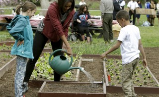 First lady Michelle Obama (center) waters vegetables with school children Nare Kande (right) and Marley Santos (left) during the spring planting on the White House South Lawn in Washington, D.C., on April 15, 2015. Photo by Gary Cameron/Reuters