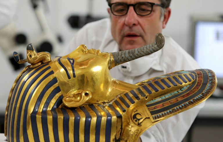 German conservator Christian Eckmann works on the restoration of the golden mask of King Tutankhamun at the Egyptian Museum in Cairo, Egypt, Oct. 20, 2015. The beard on the iconic solid-gold mask was reportedly knocked off by employees in 2014, then crudely reattached. Those involved in the process will now stand trial. Photo By Mohamed Abd El Ghany/Reuters