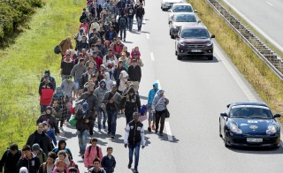 A large group of migrants, mainly from Syria, walk on a highway towards the north September 7, 2015. Many migrants, mainly from Syria and Iraq, have arrived in Denmark over the last few days. The migrants want to reach Sweden to seek asylum there. Some of the migrants arriving in central Europe have continued on to other countries, as local authorities across the continent try to accommodate the rising tide of refugees. Picture taken September 7, 2015.   REUTERS/Bax Lindhardt/Scanpix    ATTENTION EDITORS - THIS IMAGE WAS PROVIDED BY A THIRD PARTY. FOR EDITORIAL USE ONLY. NOT FOR SALE FOR MARKETING OR ADVERTISING CAMPAIGNS. THIS PICTURE IS DISTRIBUTED EXACTLY AS RECEIVED BY REUTERS, AS A SERVICE TO CLIENTS. DENMARK OUT. NO COMMERCIAL OR EDITORIAL SALES IN DENMARK. NO COMMERCIAL SALES. - RTSNJD