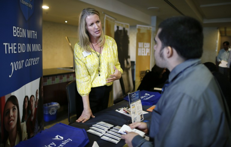 A DeVry University representative talks to job seeker at a job fair in Los Angeles, California. Photo by Lucy Nicholson/Reuters