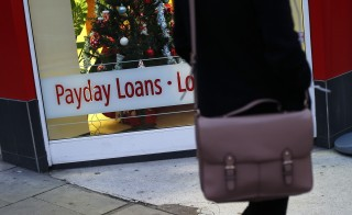 "A payday loans sign is seen in the window of Speedy Cash in northwest London November 25, 2013. Britain is to cap the cost of payday loans, stepping up its controls over the industry only a month after the regulator said that enforced price controls would be ""a very intrusive proposition"". REUTERS/Suzanne Plunkett (BUSINESS POLITICS SOCIETY) - RTX15SRM"