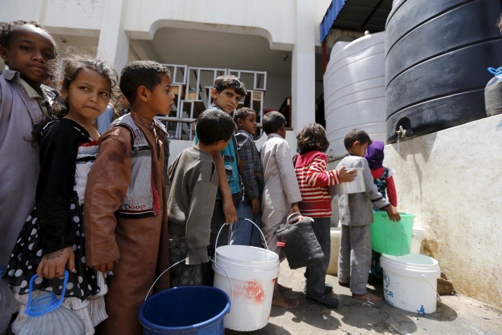 Children collect water on  Aug. 4, 2015, at a school in Yemen's capital Sanaa where they are sheltering with their families after fleeing the Houthi-controlled northern province of Saada. Photo by Khaled Abdullah/Reuters