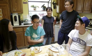 Un Bang (C) and Sung Bang (2nd R) spend time with their sons Shane (2nd L), 21, and Simon (R), 18, and Shane's girlfriend Sarah Park (L), 20, at their home in Federal Way, Washington August 8, 2015. With his parents out of work and an office job paying his bills, college junior Shane Bang remembers the anxiety he felt when his younger brother told his family he was headed to University of Washington in the fall. Then they got an unexpected lifeline. A law that took effect last month slashed tuition at public colleges and universities over the next two academic years as much as 20 percent for all Washington students, rich and poor alike. Picture taken August 8. To match Feature USA-EDUCATION/WASHINGTON     REUTERS/Jason Redmond - RTX1OH9H