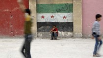 Boys play at a school's playground as one of them sits in front of a wall painted with an opposition flag in the rebel-controlled area of Aleppo's Seif al-Dawla, Syria October 25, 2015. REUTERS/Hosam Katan      EDITORIAL USE ONLY. NO RESALES. NO ARCHIVE - RTX1T67Z