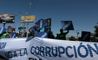 "An opposition supporter  holds up a banner reading "" No Corruption"" during a protest demanding fairer elections next year in front of the Supreme Electoral Council (CSE) building in Managua, Nicaragua, December  9, 2015. REUTERS/Oswaldo Rivas - RTX1XZL0"
