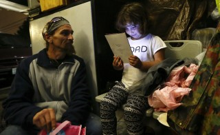 """Emma Savage, 6, opens a birthday card given to her by her dad Robert Rowe, 42, a day labourer who had just returned from a 12-hour working day to SHARE/WHEEL Tent City 3 outside Seattle, Washington October 12, 2015. SHARE and WHEEL describe themselves as self-organised, democratic organisations of homeless and formally homeless people which run several self-managed tent cities. REUTERS/Shannon Stapleton PICTURE 22 OF 35 - SEARCH """"STAPLETON TENTS"""" FOR ALL IMAGES - RTX1Z3JZ poverty,  working poor"""