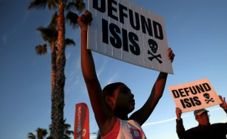 People protest against ISIS across from a makeshift memorial for victims of the San Bernardino shooting, ahead of President Obama's visit with the victims' families in San Bernardino, California on Dec. 18, 2015. The U.S. Senate will pass on a proposal by the president to expand his war powers to fight the Islamic State. Photo By Patrick T. Fallon/Reuters