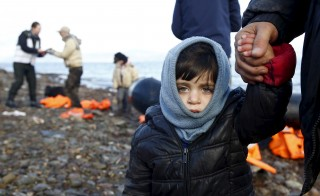 A Syrian refugee child looks on, moments after arriving on a raft with other Syrian refugees on a beach on the Greek island of Lesbos, January 4, 2016. More than 10,000 children have gone missing since entering Europe during the last two year, the EU's law enforcement agency Europol said on Sunday. Giorgos Moutafis/Reuters