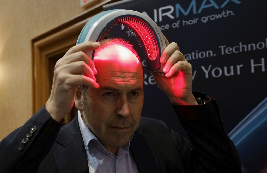 BBC television reporter Rory Cellan-Jones tries out a HairMax Laserband, a hands-free device described to treat hair loss and cause new hair growth, during the opening event at the Consumer Electronics Show in Las Vegas January 4, 2016. REUTERS/Rick Wilking - RTX211KB