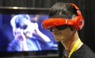 "Eric Yu of Royole models the company's foldable Smart Mobile Theater system during ""CES Unveiled,"" a preview event of the 2016 International CES trade show, in Las Vegas, Nevada January 4, 2016. The $700.00 system has noise-canceling headphones and a viewing system that is vision correctable so you don't need to wear your glasses, Yu said.  REUTERS/Steve Marcus - RTX2121Z"