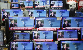 A sales assistant watches TV sets broadcasting a news report on North Korea's nuclear test, in Seoul, January 6, 2016. Photo by Kim Hong-Ji/Reuters