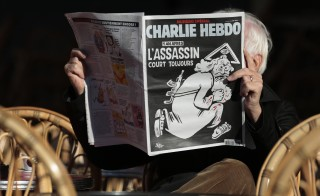 """A man reads the latest edition of French weekly newspaper Charlie Hebdo with the title """"One year on, The assassin still on the run""""  on a cafe terrasse in Nice, France, Jan. 6, 2016. Photo by Eric Gaillard/Reuters"""