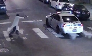 A still image from surveillance video shows a gunman (L) approaching a Philadelphia Police vehicle in which Officer Jesse Hartnett was shot shortly before midnight Jan. 7, 2016 in Philadelphia, Pennsylvania this Philadelphia Police Department image released on Friday. A gunman claiming to have pledged allegiance to Islamic State militants shot and seriously wounded a Philadelphia police officer in an ambush on his patrol car, the city's police commissioner said on Friday.  Photo By Philadelphia Police Department/Handout Via Reuters