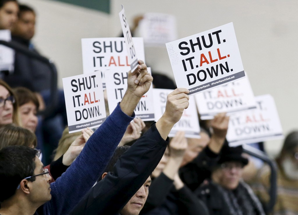 Residents of the Porter Ranch area of Los Angeles hold up signs related to a gas leak in their community during the meeting of the California Air Quality Management District in Granada Hills, California January 9, 2016. Southern California Gas Company has been tackling a Los Angeles-area natural gas leak that has been sickening nearby residents for more than two months.  REUTERS/Danny Moloshok - RTX21PNE