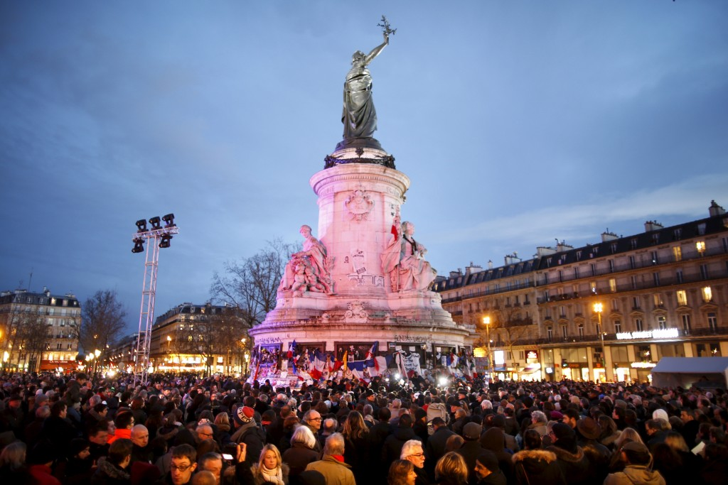 People gather at Place de la Republique square to pay tribute to the victims of last year's shooting at the French satirical newspaper Charlie Hebdo, in Paris, France, January 10, 2016. France this week commemorates the victims of last year's Islamist militant attacks on satirical weekly Charlie Hebdo and a Jewish supermarket with eulogies, memorial plaques and another cartoon lampooning religion.  REUTERS/Charles Platiau       TPX IMAGES OF THE DAY      - RTX21R2F