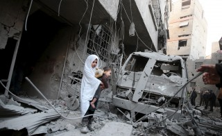 A girl carrying a baby inspects damage in a site hit by what activists said were airstrikes carried out by the Russian air force in the town of Douma, eastern Ghouta in Damascus, Syria January 10, 2016. REUTERS/Bassam Khabieh      TPX IMAGES OF THE DAY      - RTX21RG6