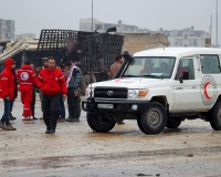 Red Crescent workers stand near their vehicles prior to inspection from rebels before heading to al Foua and Kefraya, in Idlib province, Syria January 11, 2016. An aid convoy headed for a besieged Syrian town on Monday where thousands are trapped and the United Nations says people are reported to have died of starvation. Dozens of trucks bearing the Red Crescent logo and carrying food and medical supplies left Damascus for Madaya near the Lebanese border as part of an agreement between warring sides. Another convoy was en route to two Shi'ite villages, al Foua and Kefraya in the northwestern province of Idlib 300 km (200 miles) away, the Red Cross said on its Syria Twitter account. Under the agreement, aid was to enter Madaya and the two villages simultaneously. REUTERS/Ammar Abdullah - RTX21V1U