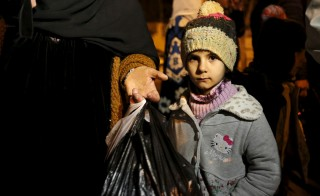 A Syrian girl waits with her family, who say they have received permission from the Syrian government to leave the besieged town, as they depart after an aid convoy entered Madaya, Syria January 11, 2016.  An aid convoy entered a besieged Syrian town on Monday where thousands have been trapped without supplies for months and people are reported to have died of starvation. Trucks carrying food and medical supplies reached Madaya near the Lebanese border and began to distribute aid as part of an agreement between warring sides, the United Nations and the Red Cross said. REUTERS/Omar Sanadiki - RTX21XMK