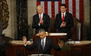 U.S. President Barack Obama reacts to cheers as he arrives at the podium to deliver his final State of the Union address. Photo by Carlos Barria/Reuters