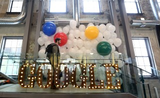 A man walks past a lit sign and balloons that were used for the unveiling of Google's new Canadian engineering headquarters in Kitchener-Waterloo, Ontario January 14, 2016. REUTERS/Peter Power - RTX22G62