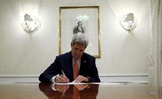 U.S. Secretary of State John Kerry signs a series of documents, including the certification to the U.S. government that International Atomic Energy Agency (IAEA) had certified Iran's compliance in their report and waivers to implement the lifting of the U.S. Congressional nuclear-related sanctions as outlined in the Joint Comprehensive Plan of Action (JCPOA), in Vienna Jan. 16, 2016.  Photos By Kevin Lamarque/Reuters