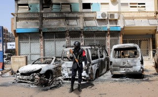 A soldier stands guard in front of burned cars across the street from Splendid Hotel in Ouagadougou, Burkina Faso, Jan. 17, 2016, a day after security forces retook the hotel from al Qaeda fighters who seized it in an assault that killed more than two dozen people from at least 18 countries and marked a major escalation of Islamist militancy in West Africa. Photo By Joe Penney/Reuters