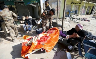 Iraqi security forces help wounded civilians as they flee the violence in the city of Ramadi, Iraq, January 16, 2016. Picture taken January 16, 2016. REUTERS/Thaier Al-Sudani - RTX22X4T