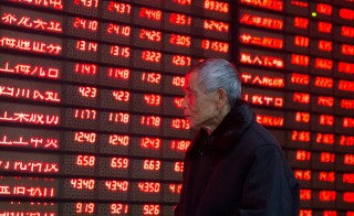 An investor walks past an electronic screen showing stock information at a brokerage house in Nanjing, Jiangsu province, January 19, 2016. China stocks rebounded roughly 3 percent on Tuesday, as weak quarterly economic data strengthened market expectations the government will unveil more stimulus moves. REUTERS/China Daily ATTENTION EDITORS - THIS PICTURE WAS PROVIDED BY A THIRD PARTY. THIS PICTURE IS DISTRIBUTED EXACTLY AS RECEIVED BY REUTERS, AS A SERVICE TO CLIENTS. CHINA OUT. NO COMMERCIAL OR EDITORIAL SALES IN CHINA. - RTX23088
