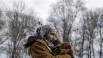 A migrant holds her baby as they wait for a train to depart to Croatia at train station in Presevo, Serbia, January 19, 2016. REUTERS/Marko Djurica - RTX2315V