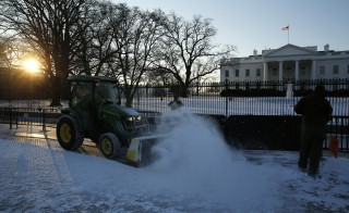 Workers plow snow from the sidewalk in front of the White House in Washington January 21, 2016. REUTERS/Jonathan Ernst - RTX23E70