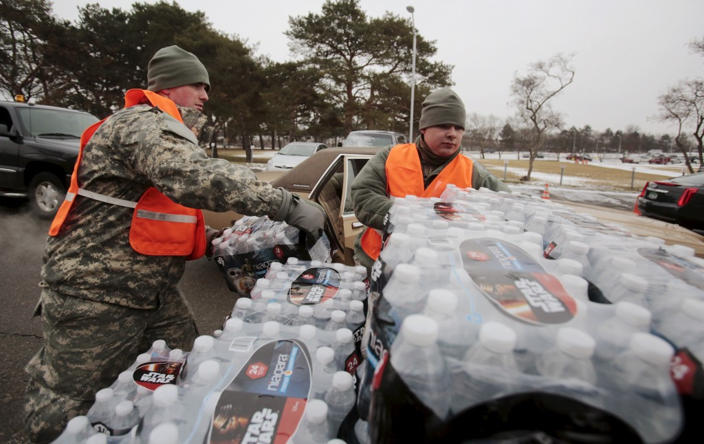 Michigan National Guard members help to distribute water to a line of residents in their cars in Flint, Michigan. Photo by Rebecca Cook/Reuters