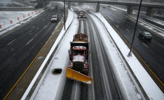 Snowplow trucks work on the roads as the snow begins to fall in Washington January 22, 2016. The leading edge of a monster snowstorm arrived on Friday afternoon in Washington, D.C., threatening to dump as many as 30 inches (76 cm) of powder on parts of the Middle Atlantic region and bring record accumulations to the U.S. capital. After days of planning by emergency officials and a scramble by residents to stock up on supplies, the blizzard got underway in the nation's capital at about 1 p.m.  REUTERS/Jonathan Ernst  - RTX23LSX