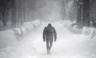 A man walks along a street covered by snow during a winter storm in Washington Jan. 23, 2016. A winter storm dumped nearly 2 feet of snow on the suburbs of Washington, D.C., on Saturday before moving on to Philadelphia and New York, paralyzing road, rail and airline travel along the U.S. East Coast. Photo By Carlos Barria/Reuters