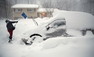 A man tries to dig out his car in Falls Church, Virginia, as a blizzard hits the east coast January 23, 2016.  REUTERS/Kevin Lamarque - RTX23Q50