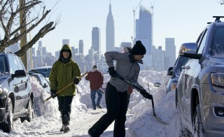 Residents clear their street of snow in Union City, New Jersey, across the Hudson River from Midtown Manhattan, after the second-biggest winter storm in New York history, Jan. 24, 2016. Photo By Rickey Rogers/Reuters