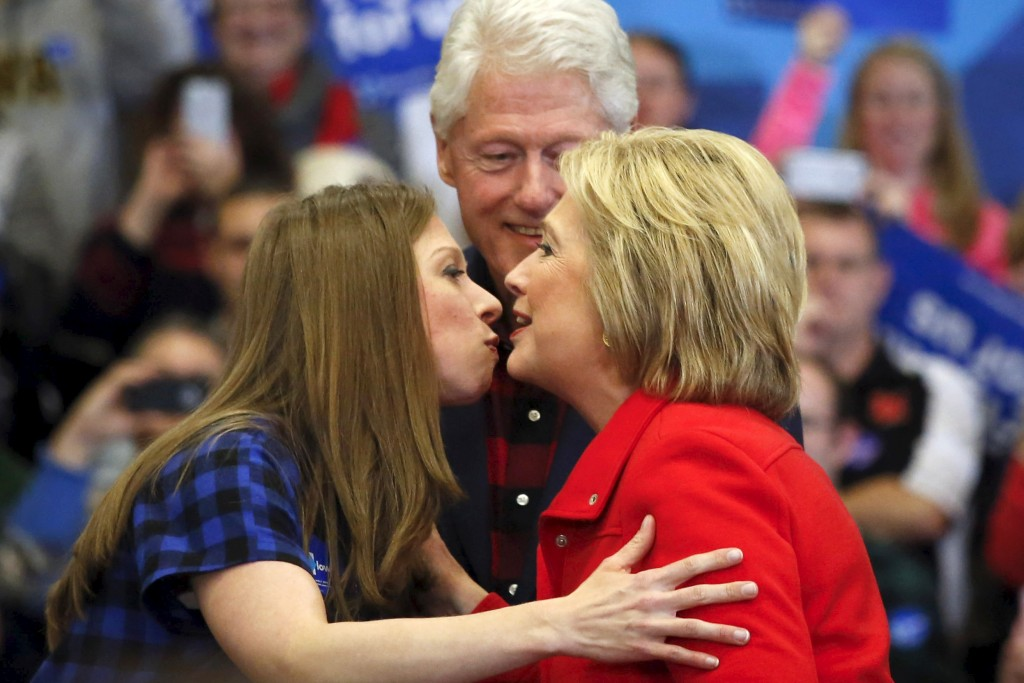 U.S. Democratic presidential candidate Hillary Clinton (R) kisses her daughter Chelsea Clinton (L) as former U.S. President Bill Clinton is seen in the background during a campaign rally at Washington High School in Cedar Rapids, Iowa January 30, 2016.  Adrees Latif/Reuters