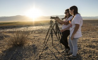 Students with Student Reporting Labs set up a shot as the sun sets over the Coachella Valley.