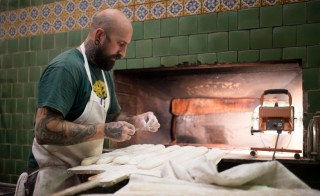 Matt Kreutz, founder of Firebrand Artisan Breads in Oakland, California, prepares loaves for the brick oven. Photo courtesy of Inner City Advisors